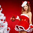 Beautiful young woman in Santa Claus clothes holding presents ov — Stockfoto