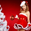 Beautiful young woman in Santa Claus clothes holding presents ov — Stok fotoğraf