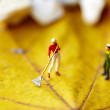 Miniature figurine  using a rake to clean up of the fallen leave - Stock Photo