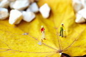 Miniature figurine using a rake to clean up of the fallen leave — Stock Photo