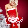 Sexy beautiful woman next to christmas white tree on red backgr — Stock Photo