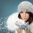 Attracive girl in santa cloth blowing snow from hands. — Stock Photo