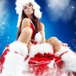 Christmas gifts. Woman wrapping christmas presents wearing santa - Foto de Stock