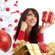 Beautiful girl with gift box next to white christmas tree — Stock Photo #7861773