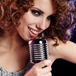 Portrait of a glamorous girl with mike singing song — Stock Photo