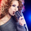 Rock star.Sexy Girl singing in retro mic - Foto de Stock  