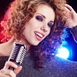 Rock star.Sexy Girl singing in retro mic - Stock Photo