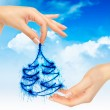 Christmas tree in hands on a blue sky — Stock Photo #7003975