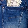 Stock Photo: Dollars in blue jeans
