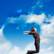 Stockfoto: Girl jump on the background of the cloudy sky