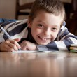 Boy does lessons lying on the floor — Stock Photo #7343893