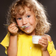 Little girl eating yogurt - Stock Photo