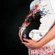 Belly pregnant woman on a black background - Stock Photo