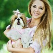 Young woman holds dog her arms - Stockfoto