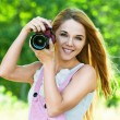 Beautiful woman holds camera - Stock Photo