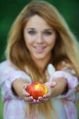 Young woman offering red apple — Stock Photo