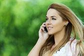 Beautiful woman talking mobile phone — Stock Photo
