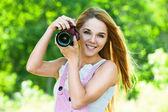 Beautiful woman holds camera — Stock Photo