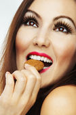 Naked woman biting biscuit — Stock Photo