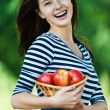 Cheerful woman basket apples - Stock Photo