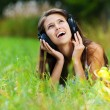 Young woman lying grass headphones fruit — Stock Photo