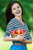 Cheerful woman basket apples — Stock Photo