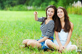Two sisters sitting grass — Stock Photo