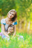Mother daughter sitting grass — Stock Photo