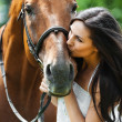 Woman kissing horse - Stock Photo