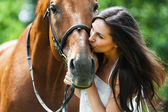 Woman kissing horse — Stock Photo