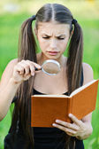 Portrait serious beautiful woman magnifier book — Stockfoto