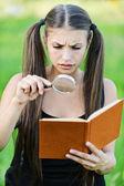 Portret ernstige mooie vrouw vergrootglas boek — Stockfoto
