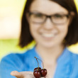 Young woman glasses black cherry palm — Stock Photo