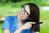 Portrait young beautiful girl glasses combs hair — Stock Photo