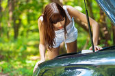 Портрет молодой женщины выглядит под капот автомобиля — Стоковое фото