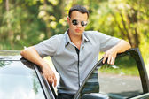 Attractive young serious man car — Stock Photo