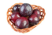 Six plums wicker basket isolated — Stock Photo