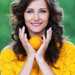 Portrait young charming woman holding tangerine — Stockfoto #7581588