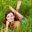 Beautiful young woman lying green grass — Stock Photo