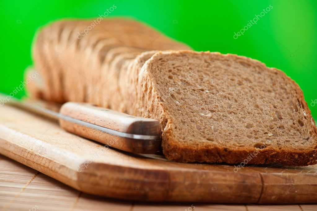 Outdoors cutting board cut rye bread, knife on background wooden table — Stock Photo #7652164