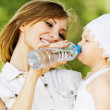 Young charming caring mother gives daughter drink — Stok fotoğraf