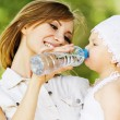 Young charming caring mother gives daughter drink — ストック写真