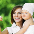 Portrait cute young woman holding arms child — Stock Photo