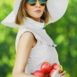 Portrait beautiful young woman serious hat holds basket apples — Stock Photo #7763809