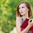 Stock Photo: Serious young beautiful woman holding red book