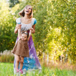 Beautiful young woman plays child field — Stock Photo