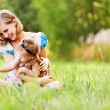 Foto Stock: Beautiful young mother daughter relaxing sitting grass