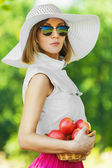 Portrait beautiful young woman serious hat holds basket apples — Stock Photo