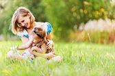 美丽的年轻母亲,女儿轻松坐草 — 图库照片
