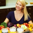 A portrait of blonde at kitchen table littered with products - Stock Photo